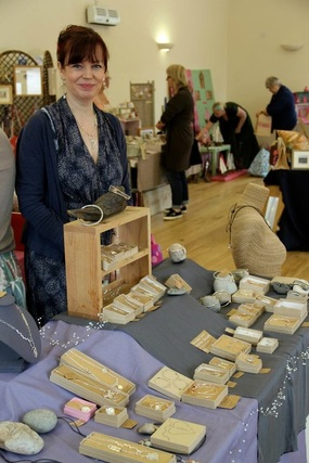 Picture of jewellery maker Sarah Jane Lewis standing in front of her stall at a previous Collective Art in Marlow event